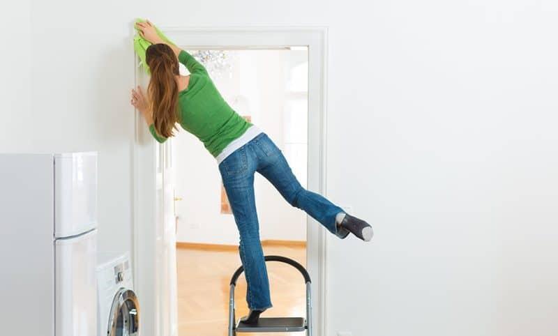Mulher em posição arriscada fazendo trabalho doméstico