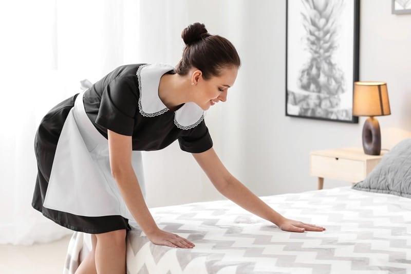 Empregada doméstica arrumando a cama